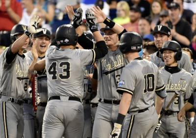 Vanderbilt first baseman Zander Wiel (43) is greeted at the dugout after he hit a solo home run in the seventh inning of an NCAA College World Series baseball game against TCU at TD Ameritrade Park in Omaha, Neb., Tuesday, June 16, 2015. (AP Photo/Mike Theiler)