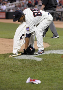 Jun 10, 2015; Minneapolis, MN, USA;  Twins bat boy gathers up the items tossed on the field by Minnesota Twins right fielder Torii Hunter (not pictured) after being ejected during the eighth inning against the Kansas City Royals at Target Field.  The Royals won 7-2 over the Twins.  Mandatory Credit: Marilyn Indahl-USA TODAY Sports