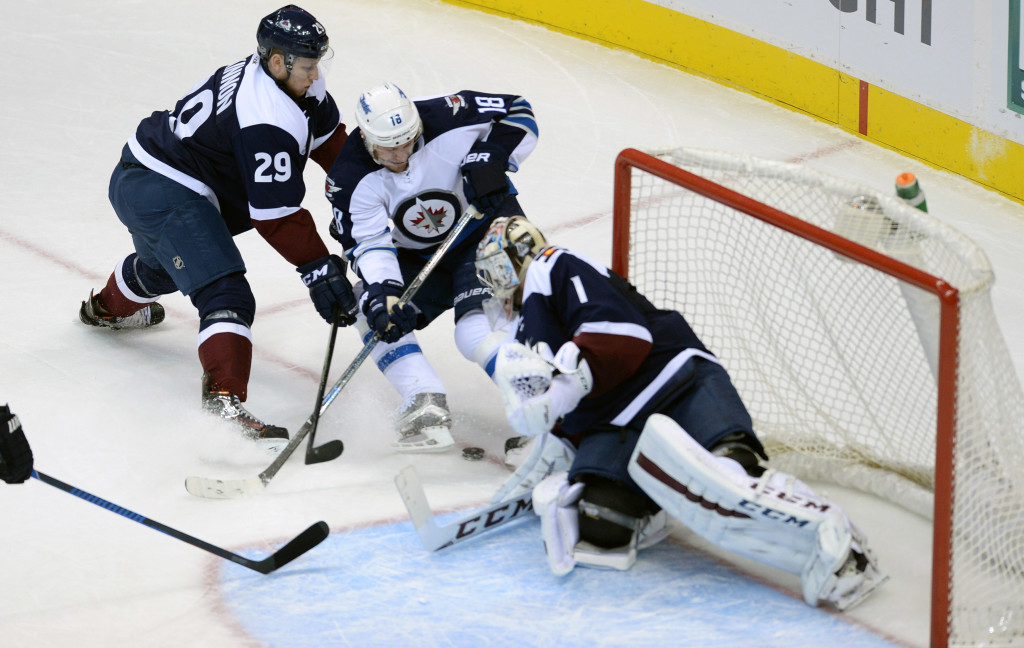 Nov 28, 2015; Denver, CO, USA; Winnipeg Jets center Bryan Little (18) attempts to score past Colorado Avalanche goalie Semyon Varlamov (1) as center Nathan MacKinnon (29) defends in the first period at the Pepsi Center. Mandatory Credit: Ron Chenoy-USA TODAY Sports