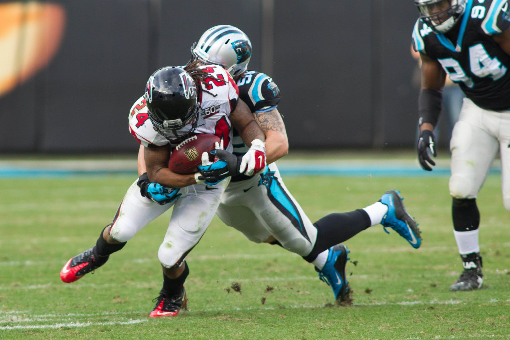 Dec 13, 2015; Charlotte, NC, USA; Atlanta Falcons running back Devonta Freeman (24) is ackled by Carolina Panthers middle linebacker A.J. Klein (56) during the third quarter at Bank of America Stadium. Panthers defeated the Falcons 38-0. Mandatory Credit: Jeremy Brevard-USA TODAY Sports